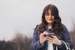 Closeup portrait young girl looking at phone messaging. SMS. Closeup portrait young girl looking at phone and messaging with copy space Royalty Free Stock Photography