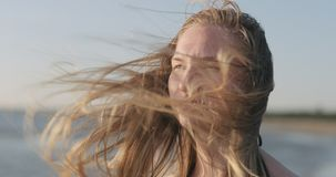 Closeup portrait of young girl standing on a beach and wind blows her hair stock image