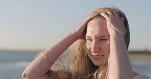 Closeup portrait of young girl standing on a beach and wind blows her hair royalty free stock photography