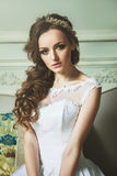Closeup portrait of young gorgeous bride sitting in antique inte. Rior. White wedding dress. Glamour hairstyle and makeup Stock Photo
