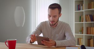 Closeup portrait of young handsome caucasian businessman browsing on the tablet indoors in the apartment.  stock video
