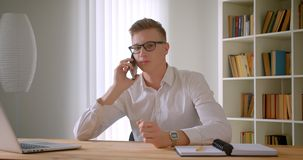 Closeup portrait of young handsome caucasian businessman in glasses having a phone call indoors in the office.  stock video