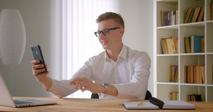 Closeup portrait of young handsome caucasian businessman in glasses having a video call on the phone talking cheerfully. Indoors in the office stock video footage