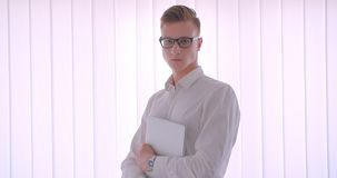 Closeup portrait of young handsome caucasian businessman in glasses holding a laptop indoors in a white room.  stock video footage