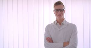 Closeup portrait of young handsome caucasian businessman in glasses looking at camera smiling happily with his arms. Crossed over chest indoors in a white room stock video footage