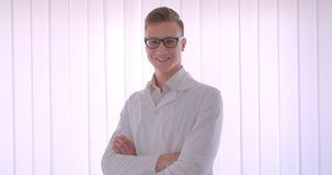 Closeup portrait of young handsome caucasian businessman in glasses looking at camera smiling happily indoors in a white. Room stock video
