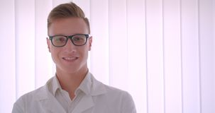 Closeup portrait of young handsome caucasian businessman in glasses looking at camera smiling happily standing indoors. In a white room stock footage