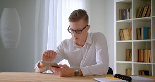 Closeup portrait of young handsome caucasian businessman in glasses using the tablet looking at camera indoors in the. Office stock video footage
