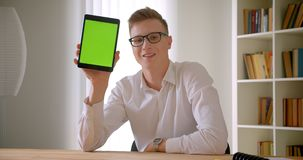Closeup portrait of young handsome caucasian businessman in glasses using the tablet and showing green chroma screen to. Camera indoors in the office stock video footage