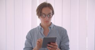 Closeup portrait of young handsome caucasian businessman in glasses using the tablet standing indoors in the office stock footage