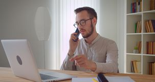 Closeup portrait of young handsome caucasian businessman having a formal phone call sitting in front of the laptop. Indoors in the apartment stock video