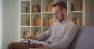Closeup portrait of young handsome caucasian businessman reading a book looking at camera sitting on the couch indoors. In the apartment stock video