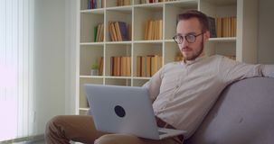 Closeup portrait of young handsome caucasian businessman typing on the laptop looking at camera smiling happily sitting. On the couch indoors in the apartment stock video footage