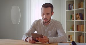 Closeup portrait of young handsome caucasian businessman using the tablet indoors in the apartment with bookshelves on. The background stock footage