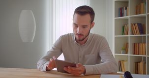 Closeup portrait of young handsome caucasian businessman using the tablet looking at camera indoors in the apartment.  stock video footage