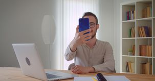 Closeup portrait of young handsome caucasian businessmantaking selfies on the phone sitting in front of the laptop. Indoors in the apartment indoors stock video footage