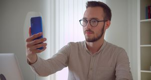 Closeup portrait of young handsome caucasian businessmantaking selfies on the phone smiling happily sitting in front of. The laptop indoors in the apartment stock video
