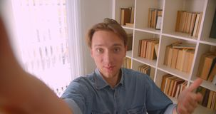 Closeup portrait of young handsome caucasian male blogger streaming live in library indoors.  stock video footage