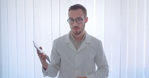 Closeup portrait of young handsome caucasian male doctor holding a tablet and showing green chroma screen to camera in stock video footage