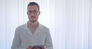 Closeup portrait of young handsome caucasian male doctor looking at camera smiling happily holding a tablet in the white. Apartment stock footage