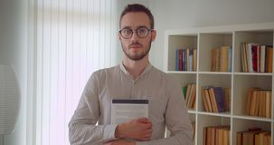 Closeup portrait of young handsome caucasian male student in eyeglasses holding a book looking at camera standing in the. Apartment indoors stock footage