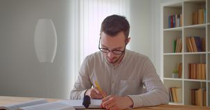 Closeup portrait of young handsome caucasian male student in eyeglasses studying and using the tablet taking notes. Looking at camera in the college library stock footage