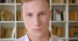 Closeup portrait of young handsome caucasian male student looking at camera in the college library.  stock video