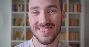 Closeup portrait of young handsome caucasian male student looking at camera smiling with excitement in the college. Library with bookshelves on the background stock video footage