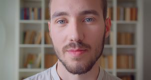 Closeup portrait of young handsome caucasian male student looking at camera smiling happily in the college library with. Bookshelves on the background stock video
