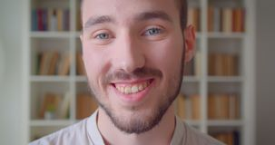 Closeup portrait of young handsome caucasian male student looking at camera smiling happily in the college library.  stock footage