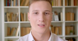 Closeup portrait of young handsome caucasian male student smiling cheerfully looking at camera in the college library.  stock footage