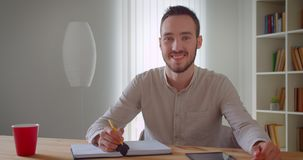 Closeup portrait of young handsome caucasian male student studying and using the tablet looking at camera smiling. Cheerfully in the college library indoors stock video