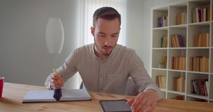 Closeup portrait of young handsome caucasian male student studying and using the tablet looking at camera smiling. Cheerfully in the college library stock video footage