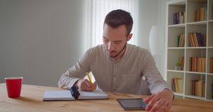 Closeup portrait of young handsome caucasian male student studying and using the tablet looking at camera smiling. Happily in the college library stock video