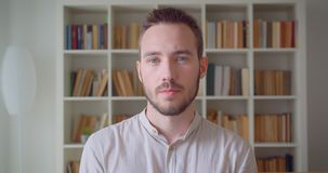 Closeup portrait of young handsome caucasian male student turning and looking at camera in the college library.  stock video