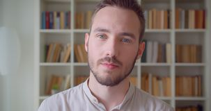 Closeup portrait of young handsome caucasian male student turning and looking at camera smiling cheerfully in the. College library stock video footage