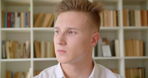 Closeup portrait of young handsome caucasian student looking at camera in the college library stock footage
