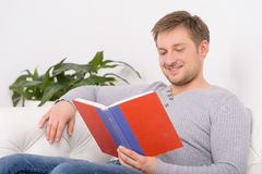 Closeup portrait of young, handsome man reading book. Stock Image