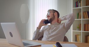 Closeup portrait of young handsome relaxed caucasian businessman having a phone call sitting in front of the laptop. Indoors in the apartment stock video footage