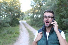 Closeup portrait, young happy ecstatic man with hand on wide open eyes and mouth talking on cell phone, outdoors outside. Background royalty free stock photo