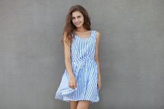 Closeup portrait of young happy smiling beautiful woman in light dress with long brunette curly hair posing against wall on a warm Royalty Free Stock Photo