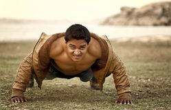Young Healthy Man. Closeup portrait, young healthy handsome man performing pushup outside at bank of river stock image