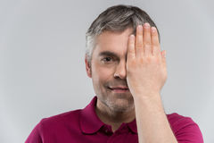 Closeup portrait of young man covering his eye. Royalty Free Stock Photos