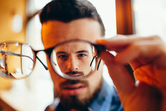 Closeup portrait of young man with glasses, who has eyesight problems Royalty Free Stock Images