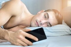 Closeup portrait of a young man, looks at messages on a smartphone in bed at home in the morning. the concept-social networking, t. Echnology, Internet Stock Photos