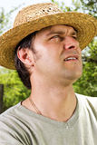 Closeup portrait of a young man with straw hat looking up Royalty Free Stock Images