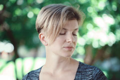 Closeup portrait of young middle aged white caucasian girl woman with short hair stylish haircut  in tshirt with closed eyes Stock Photo