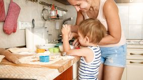 Closeup portrait of young mother teaching her toddler son making cookies. Child with parent baking desserts on baking. Closeup portrait of young mother teaching royalty free stock photo