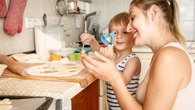 Closeup portrait of young mother teaching her toddler son making cookies. Child with parent baking desserts on baking. Closeup portrait of young mother teaching stock photo