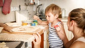 Closeup portrait of young mother with toddler boy holding baking pan and making cookies on kitchen. Closeup portrait of mother with toddler boy holding baking royalty free stock photos
